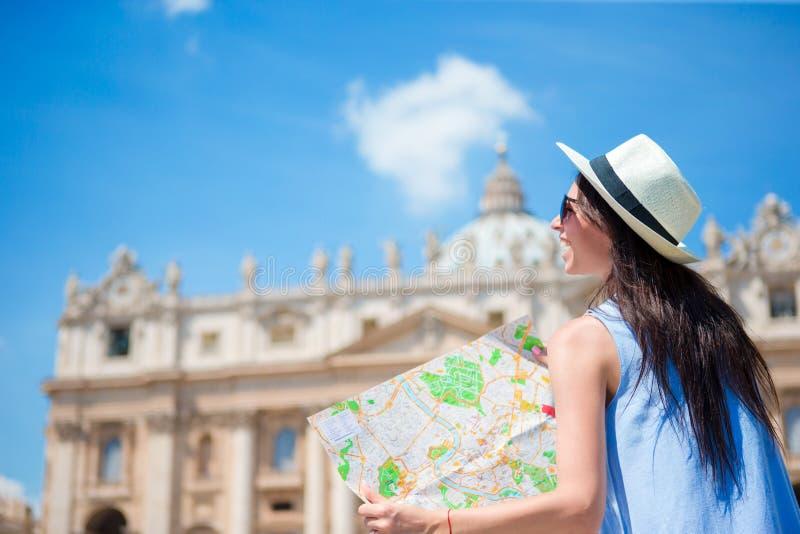 Jovem mulher feliz com o mapa da cidade na Cidade do Vaticano e na igreja da basílica de St Peter, Roma, Itália Mulher do turista imagens de stock