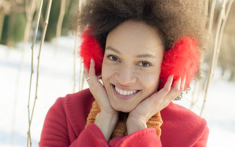 Jovem mulher feliz com o morno nas orelhas que aprecia a luz do sol do inverno imagens de stock