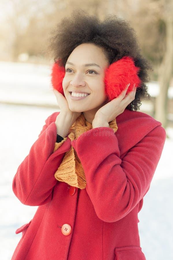 Jovem mulher feliz com o morno nas orelhas que aprecia a luz do sol do inverno imagem de stock