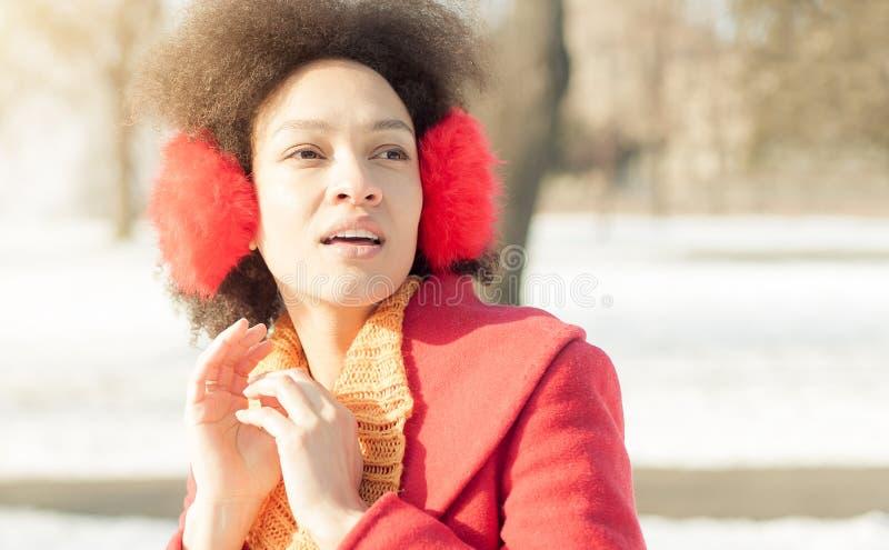 Jovem mulher feliz com o morno nas orelhas que aprecia a luz do sol do inverno fotos de stock