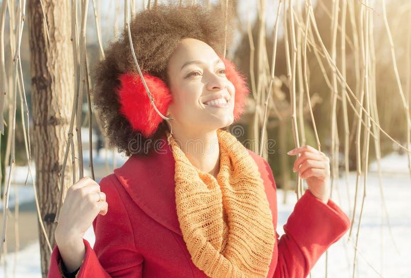 Jovem mulher feliz com o morno nas orelhas que aprecia a luz do sol do inverno imagem de stock royalty free