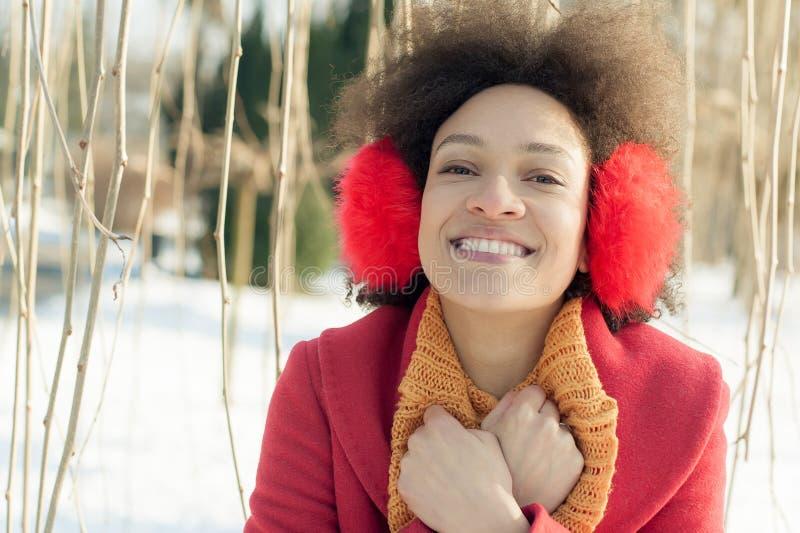 Jovem mulher feliz com o morno nas orelhas que aprecia a luz do sol do inverno fotografia de stock