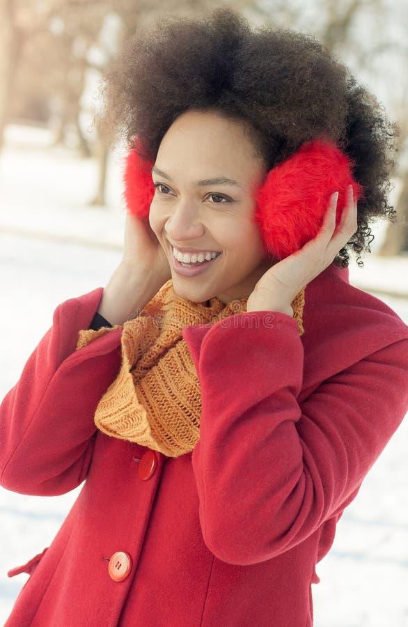 Jovem mulher feliz com o morno nas orelhas que aprecia a luz do sol do inverno fotografia de stock royalty free