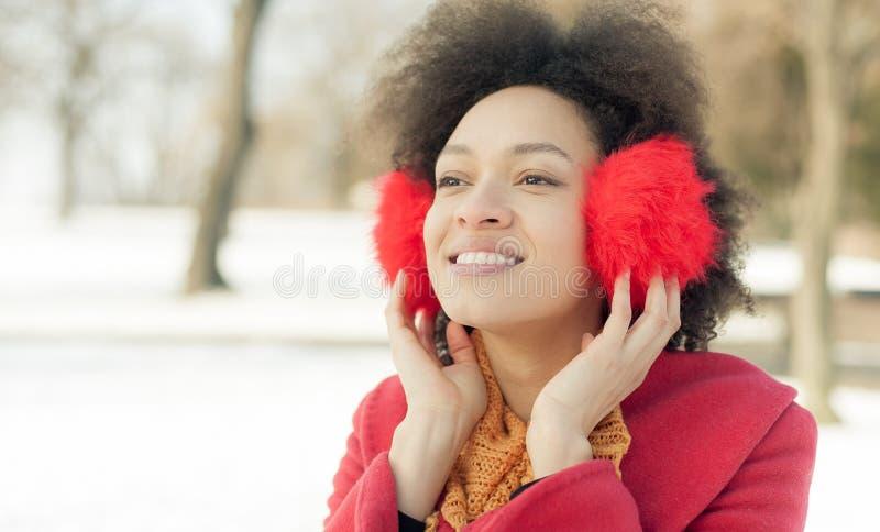 Jovem mulher feliz com o morno nas orelhas que aprecia a luz do sol do inverno foto de stock