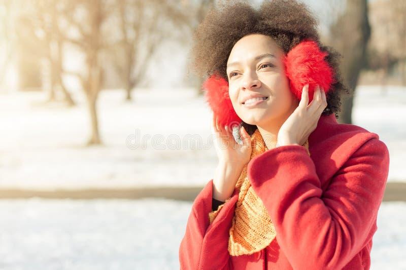 Jovem mulher feliz com o morno nas orelhas que aprecia a luz do sol do inverno fotos de stock royalty free