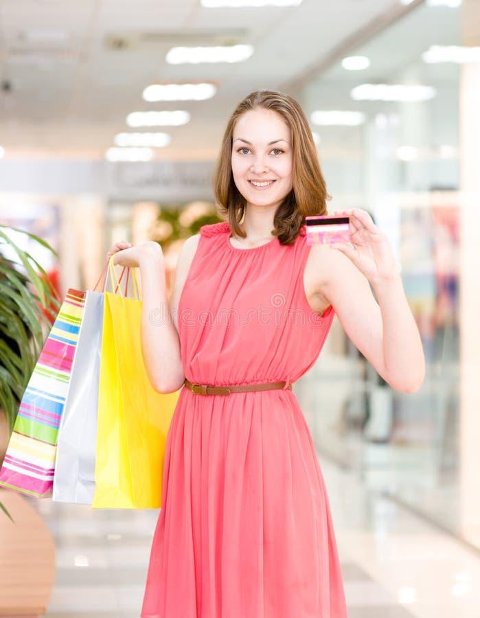 Jovem mulher feliz com os sacos de compras que mostram o cartão de crédito fotografia de stock royalty free