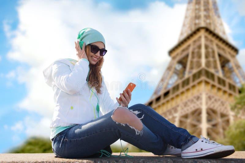 Jovem mulher feliz com smartphone e fones de ouvido fotos de stock royalty free