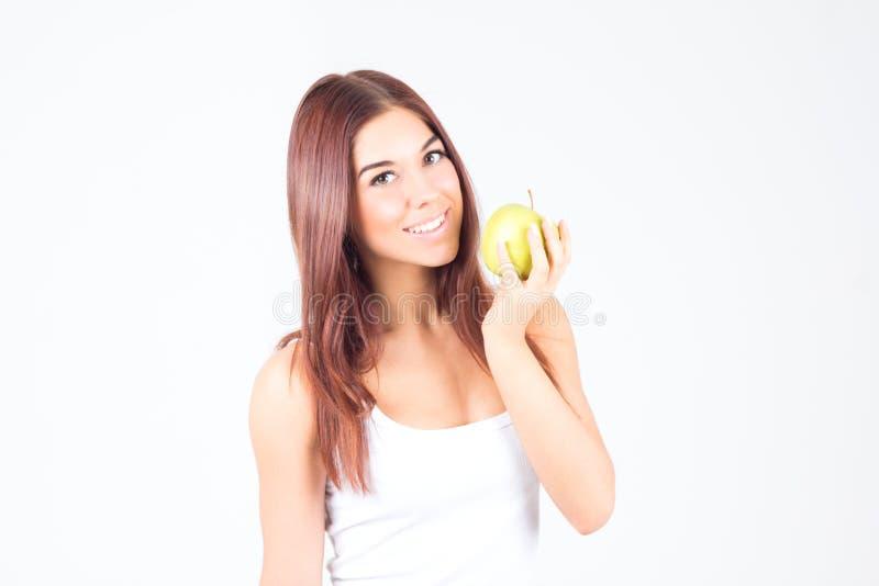 Jovem mulher feliz com sorriso com os dentes que guardam uma maçã nas mãos Estilo de vida saudável fotos de stock royalty free