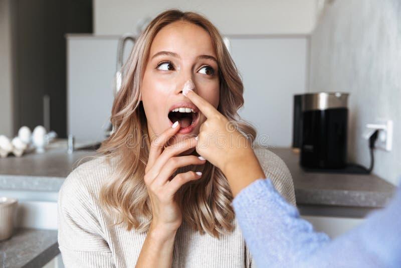 Jovem mulher feliz com sua cozinha da irmã mais nova dentro em casa que cozinha a padaria dos sweeties que tem o divertimento fotografia de stock