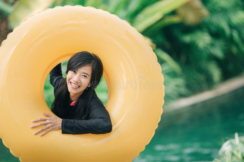 Jovem mulher feliz com tubo em um recurso do parque da água imagens de stock