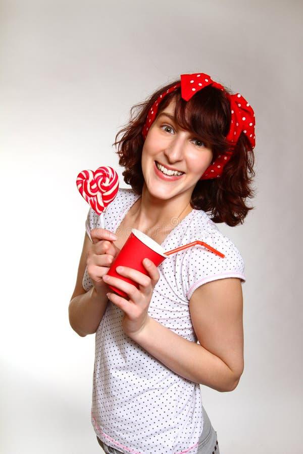 Jovem mulher feliz com um pirulito e um copo em um b cinzento fotos de stock royalty free