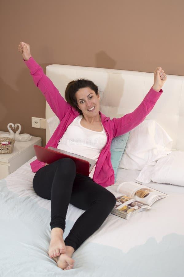 Jovem mulher feliz com um portátil e os braços acima no quarto imagens de stock
