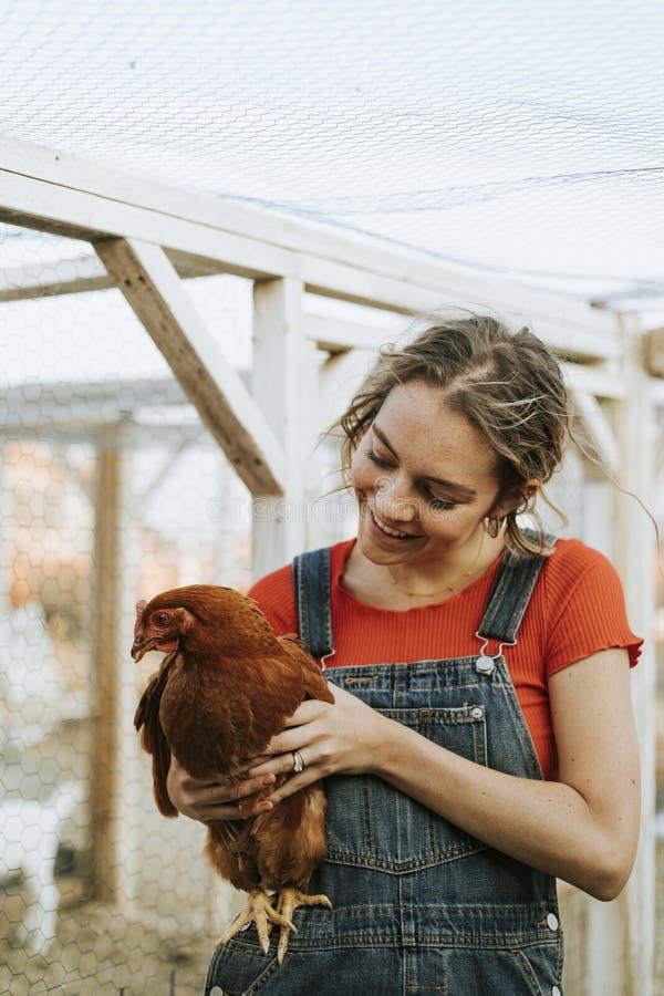 Jovem mulher feliz com uma galinha marrom imagens de stock royalty free
