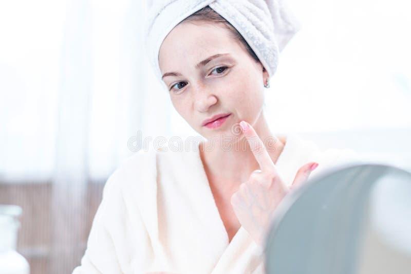 Jovem mulher feliz com uma toalha em sua cabeça que olha sua pele em um espelho Higiene e cuidado oportunos para a pele fotografia de stock