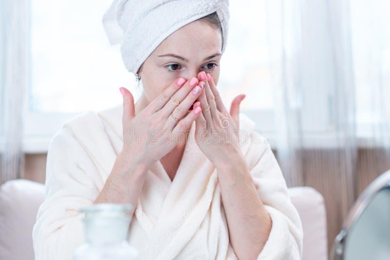 Jovem mulher feliz com uma toalha em sua cabeça que olha sua pele em um espelho Higiene e cuidado oportunos para a pele fotos de stock royalty free
