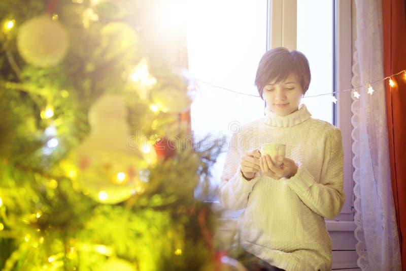 Jovem mulher feliz com xícara de café ou chá em casa sobre a árvore de Natal imagem de stock