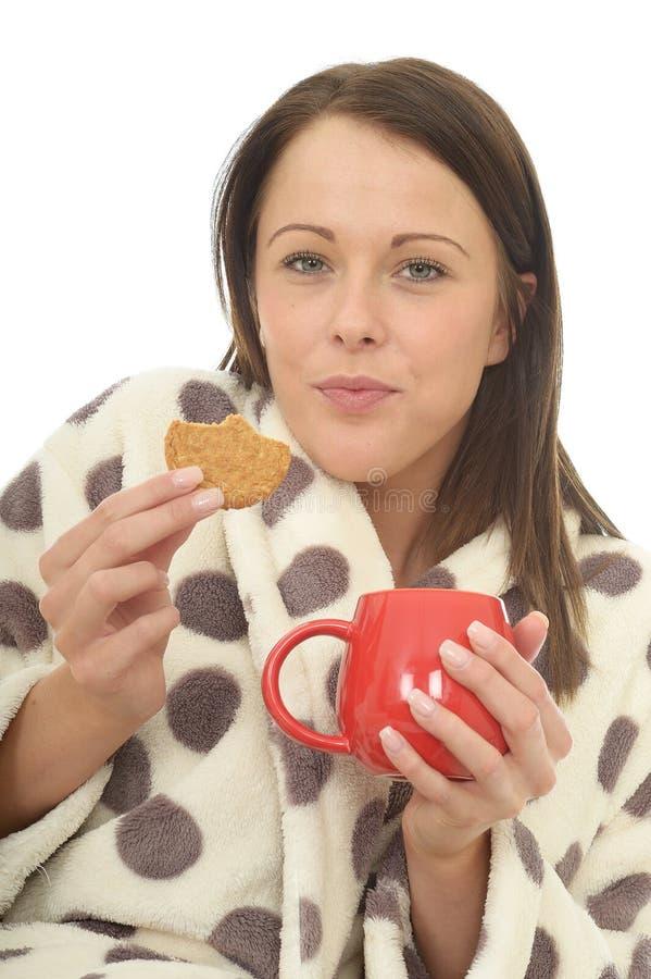 Jovem mulher feliz confortável relaxado atrativa que come biscoitos e que bebe o chá imagem de stock