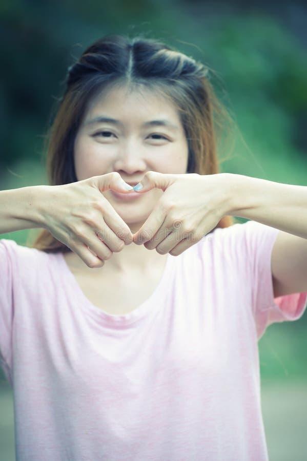 Jovem mulher feliz de Ásia que faz o sinal do coração com mãos fotos de stock