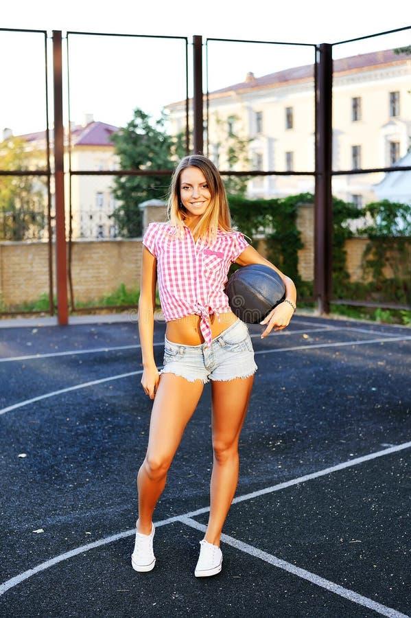 Jovem mulher feliz do retrato que guarda o basquetebol na corte exterior imagem de stock royalty free