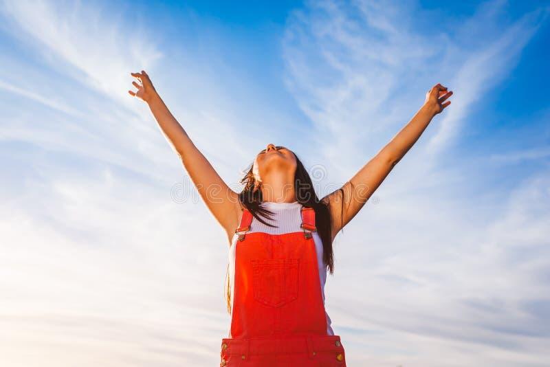 Jovem mulher feliz e livre que aumenta os braços no fundo do céu azul Liberdade Estilo de vida saudável imagens de stock royalty free