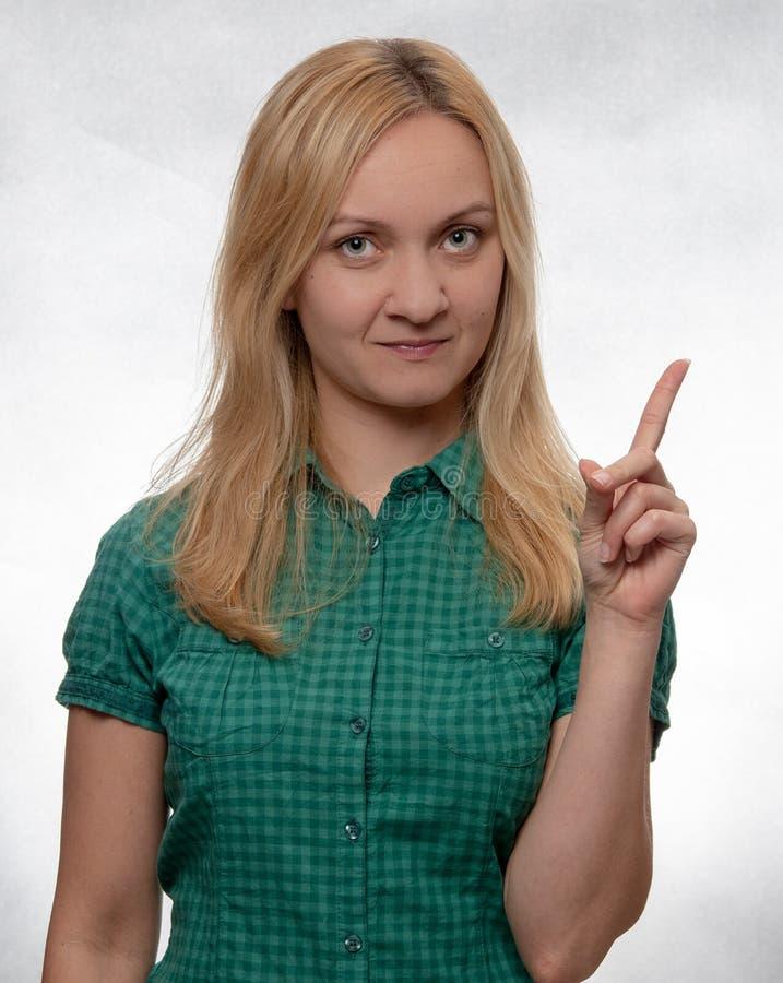 Jovem mulher feliz e sorrindo na camisa verde ocasional que aponta acima e que olha em linha reta na câmera imagem de stock
