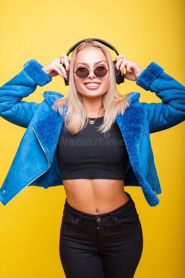 Jovem mulher feliz em óculos de sol redondos do vintage com fones de ouvido fotos de stock royalty free