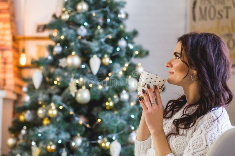 Jovem mulher feliz em vestir feito malha branco com xícara de café ou chá em casa foto de stock royalty free