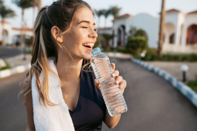 Jovem mulher feliz entusiasmado do retrato do close up que sorri com olhos fechados para expor-se ao sol com a garrafa da água Sp imagens de stock
