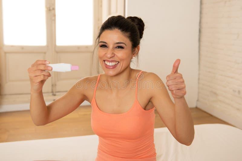 Jovem mulher feliz, entusiasmado que guarda um teste de gravidez que olha o resultado positivo na alegria fotos de stock royalty free