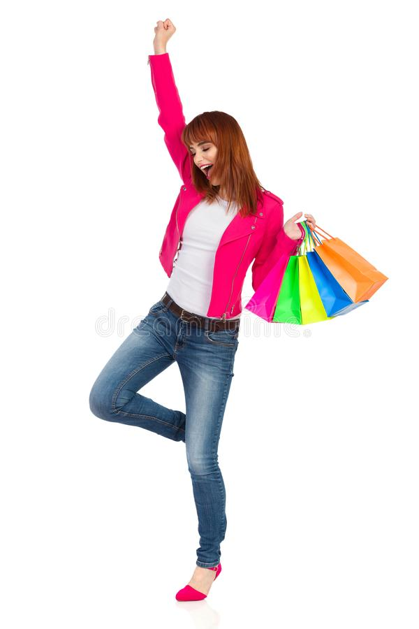 A jovem mulher feliz está estando em um pé e em sacos de compras levando imagem de stock royalty free