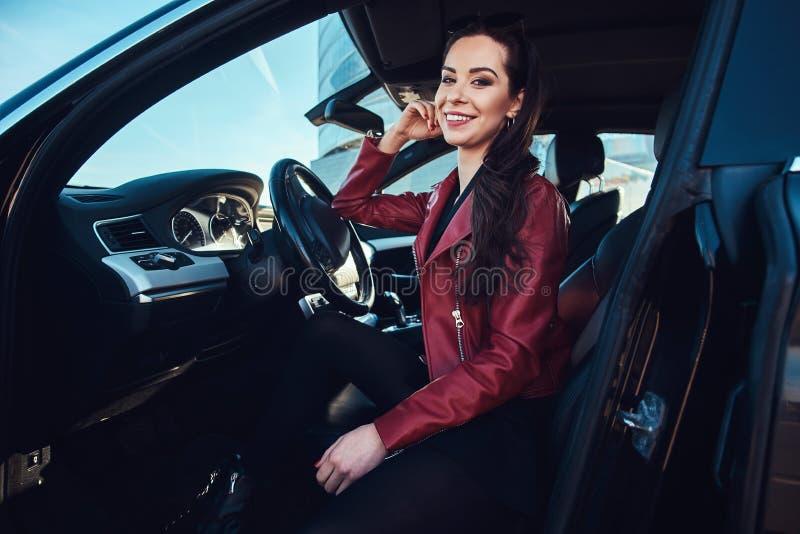 A jovem mulher feliz está sentando-se em seu carro novo fotos de stock royalty free