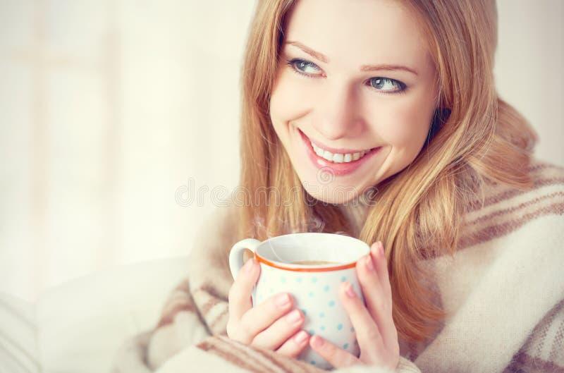 A jovem mulher feliz está sob uma cobertura e uma xícara de café na manhã do inverno em casa foto de stock