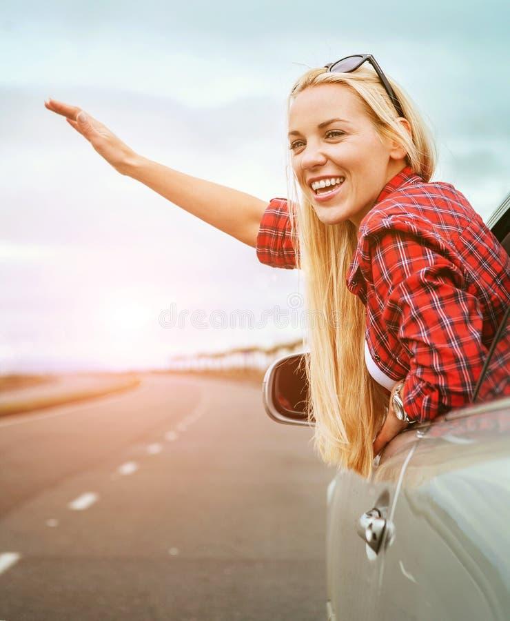 A jovem mulher feliz faz um grande gesto da janela de carro foto de stock