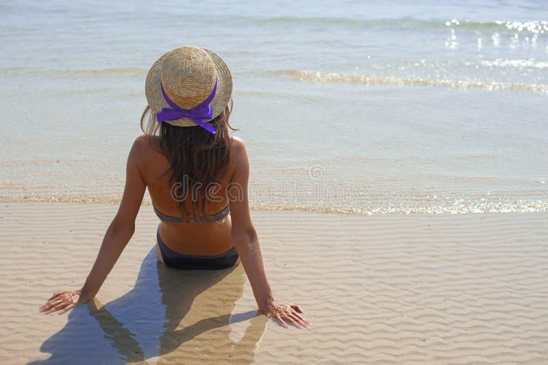 Jovem mulher feliz ? moda que relaxa na praia menina que senta-se e que bronzea-se na praia perto do mar com ondas, tempo morno e imagem de stock royalty free