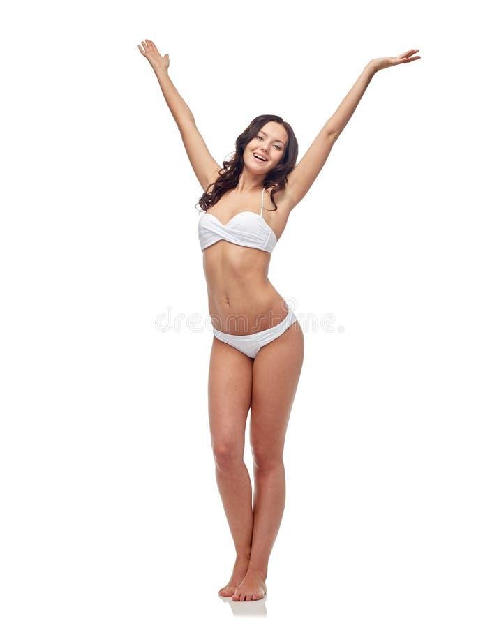 Jovem mulher feliz na dança branca do roupa de banho do biquini fotos de stock royalty free