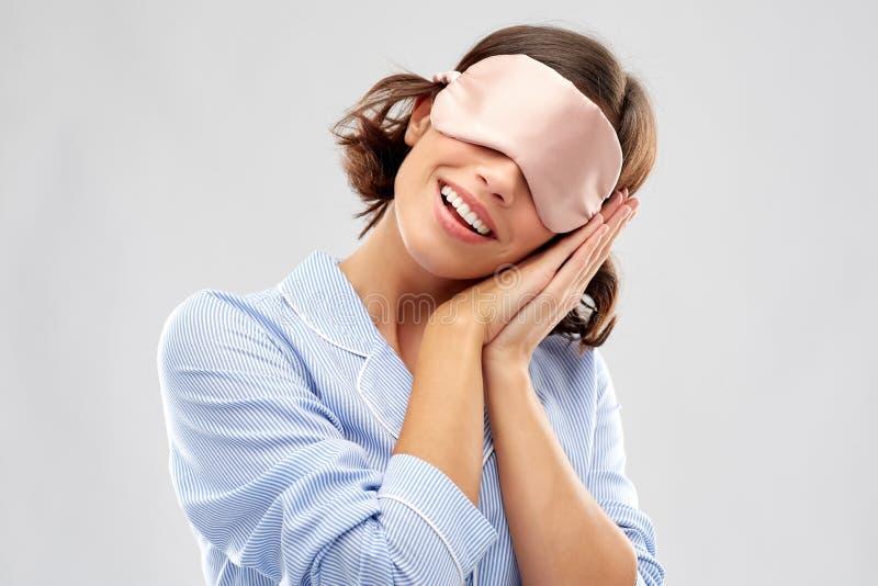 Jovem mulher feliz na m?scara do sono do pijama e do olho fotos de stock royalty free