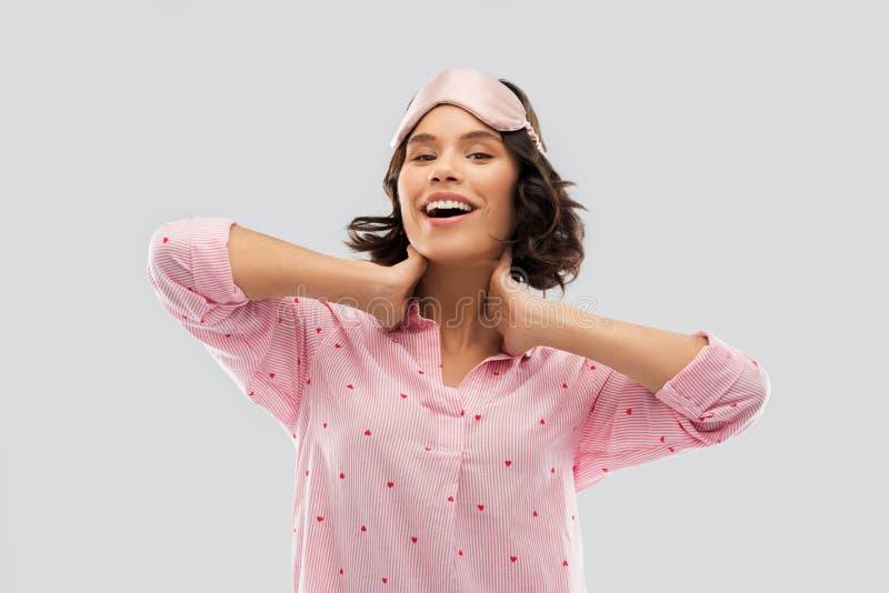 Jovem mulher feliz na m?scara do sono do pijama e do olho foto de stock