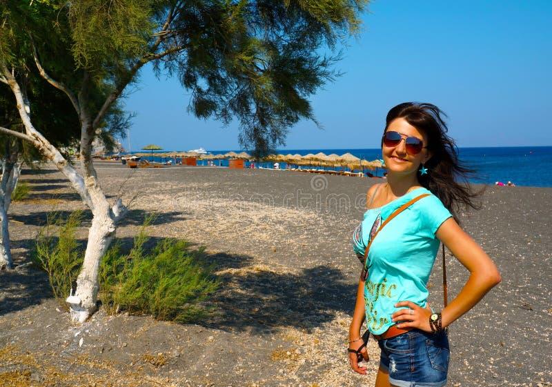 Jovem mulher feliz na praia preta fotos de stock