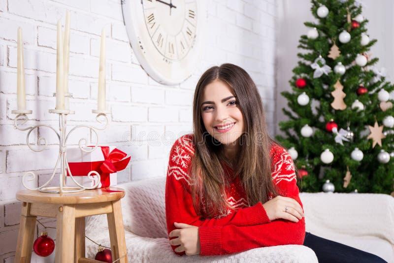 Jovem mulher feliz na sala de visitas decorada com árvore de Natal fotografia de stock