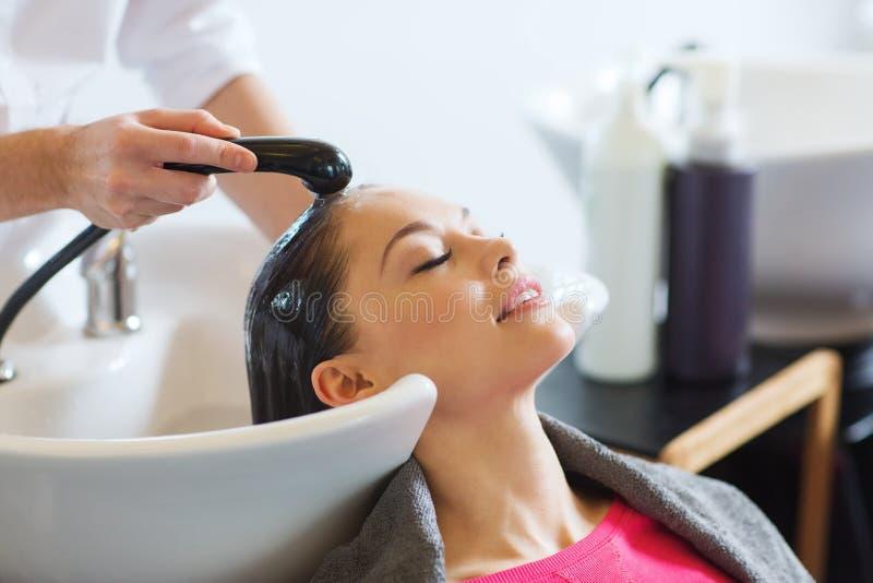 Jovem mulher feliz no cabeleireiro imagens de stock