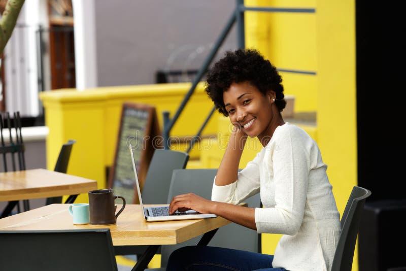 Jovem mulher feliz no café exterior com portátil fotos de stock