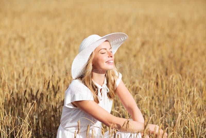 Jovem mulher feliz no chapéu do sol no campo de cereal imagem de stock royalty free