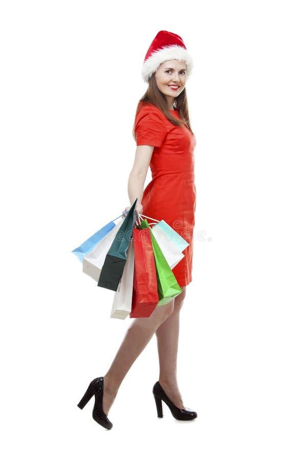 Jovem mulher feliz no chapéu vermelho do vestido e do ajudante de Santa que guarda sacos de compras Isolado sobre o branco fotos de stock royalty free