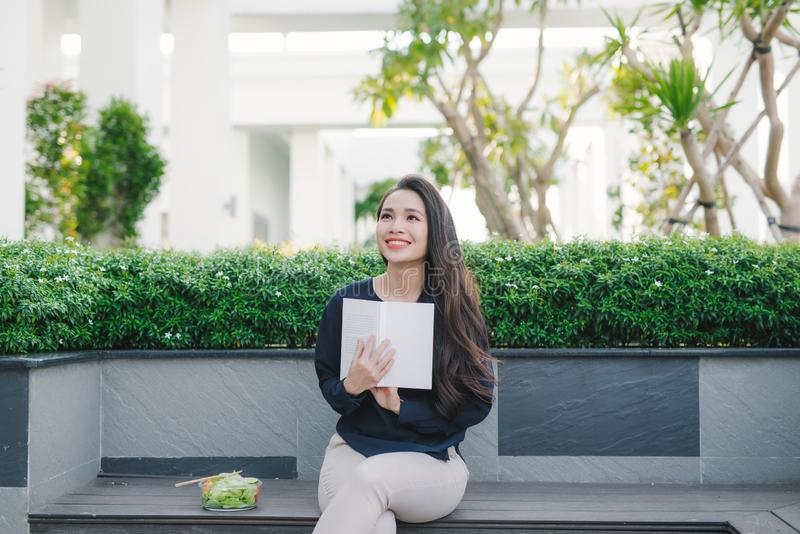 Jovem mulher feliz no parque no livro de leitura ensolarado do dia de verão Menina bonita alegre no dia bonito imagem de stock