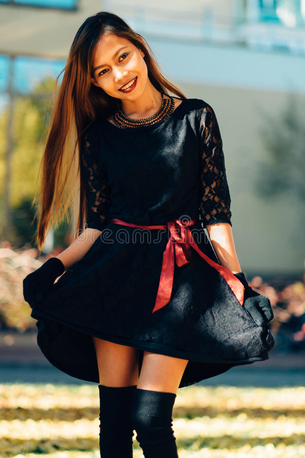 Jovem mulher feliz no parque no dia ensolarado do outono, sorrindo Menina bonita alegre no estilo retro preto da forma do outono  imagens de stock