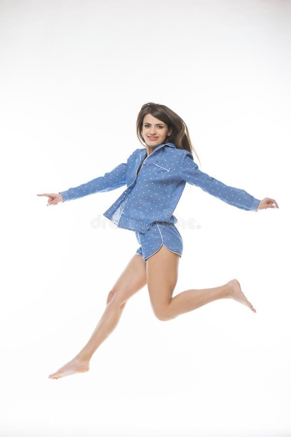 Jovem mulher feliz no salto dos pijamas isolada no fundo branco imagem de stock