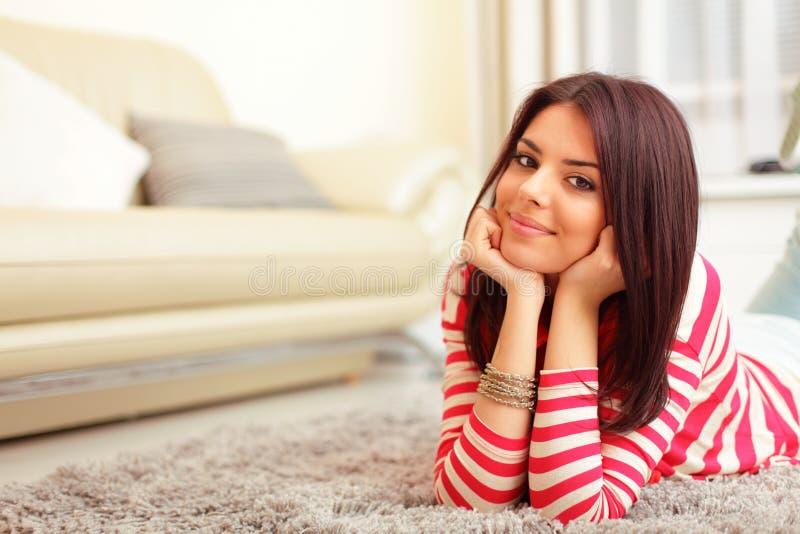 Jovem mulher feliz no sofá imagem de stock