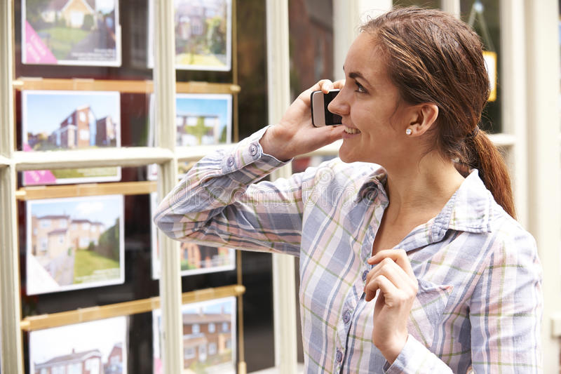 Jovem mulher feliz no telefone fora dos agentes imobiliários fotografia de stock royalty free