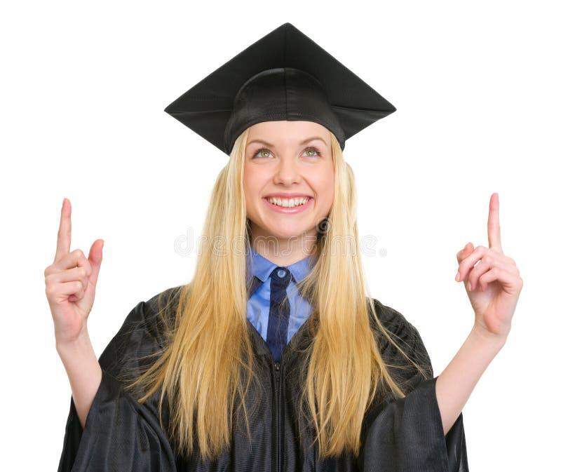 Jovem mulher feliz no vestido da graduação que aponta acima fotografia de stock