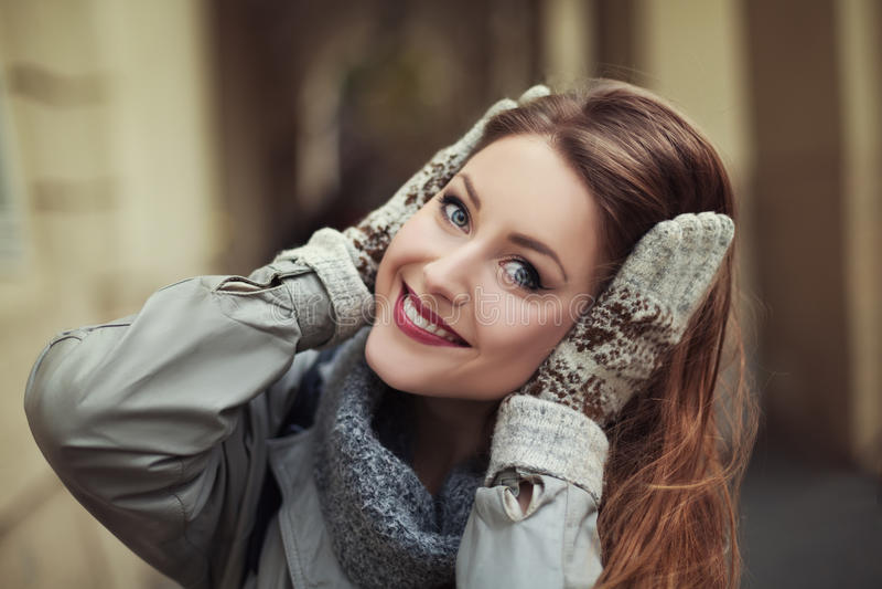 Jovem mulher feliz nos mitenes que sorri e que olha a câmera Fim acima fotos de stock